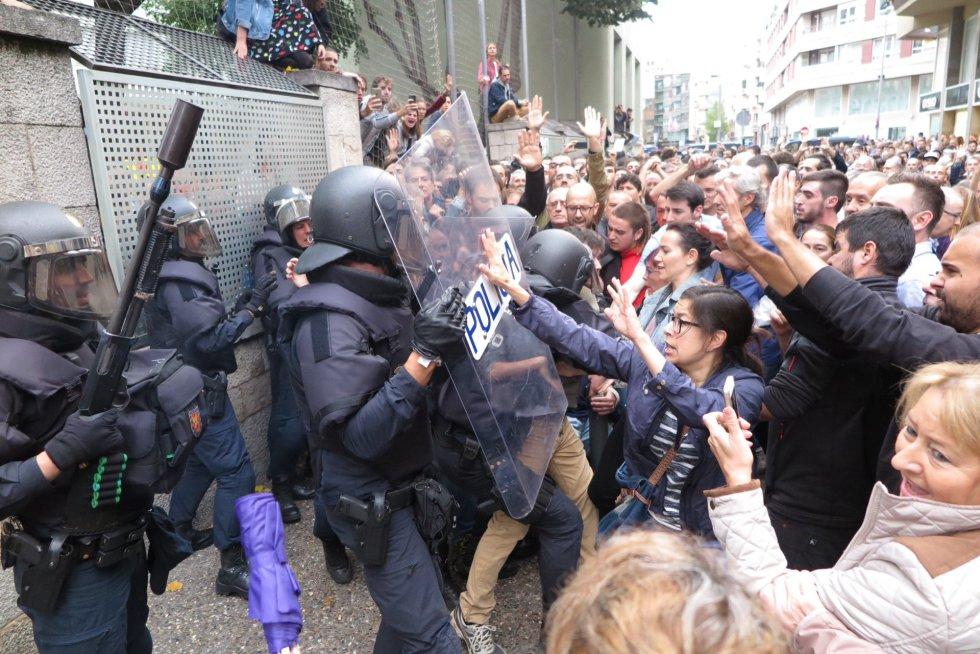 Agentes de la policía cargan contra los ciudadanos que querian entrar en el colegio electoral Verd de Gerona.
