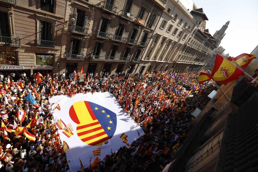 Una pancarta con las imágenes de las banderas de Cataluña, España y Europa es llevada durante la manifestación.