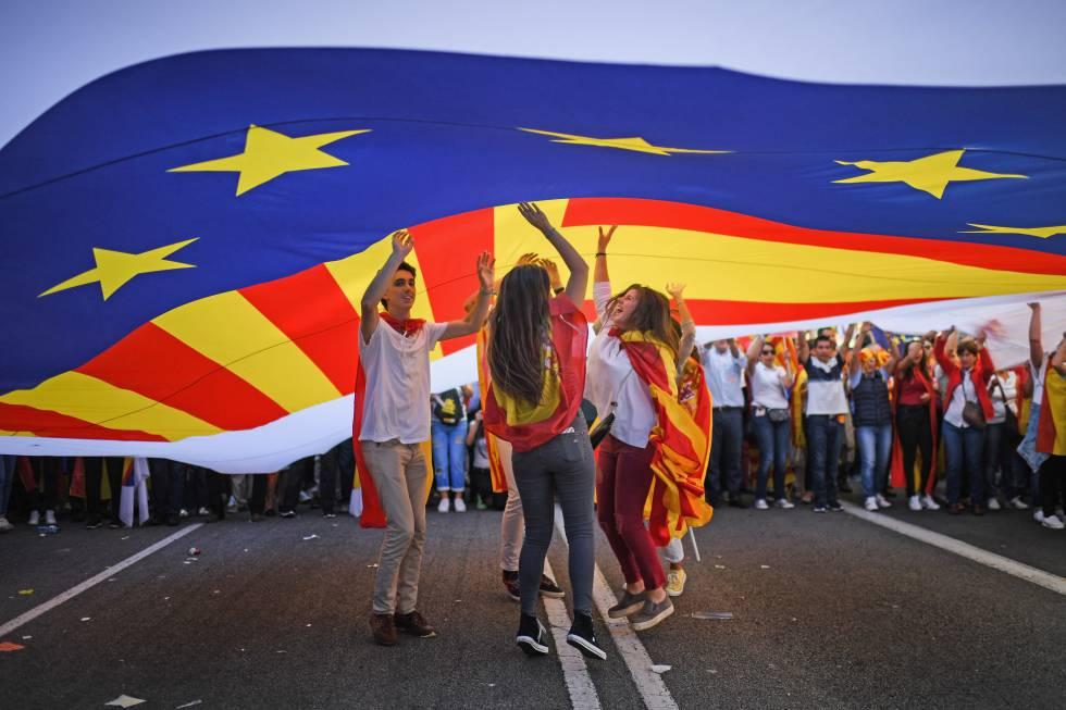 Adolescentes saltan debajo de una bandera.
