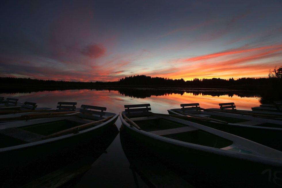 Varios botes permanecen amarrados en el lago Elbsee durante una puesta de sol en Aitrang (Alemania).