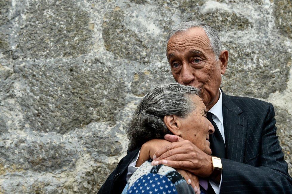 El presidente luso, Marcelo Rebelo de Sousa, besa a una mujer mientras llora, durante una visita a los municipios del centro del país afectados por los incendios forestales de la semana pasada, en Santa Comba, Vouzela (Portugal).