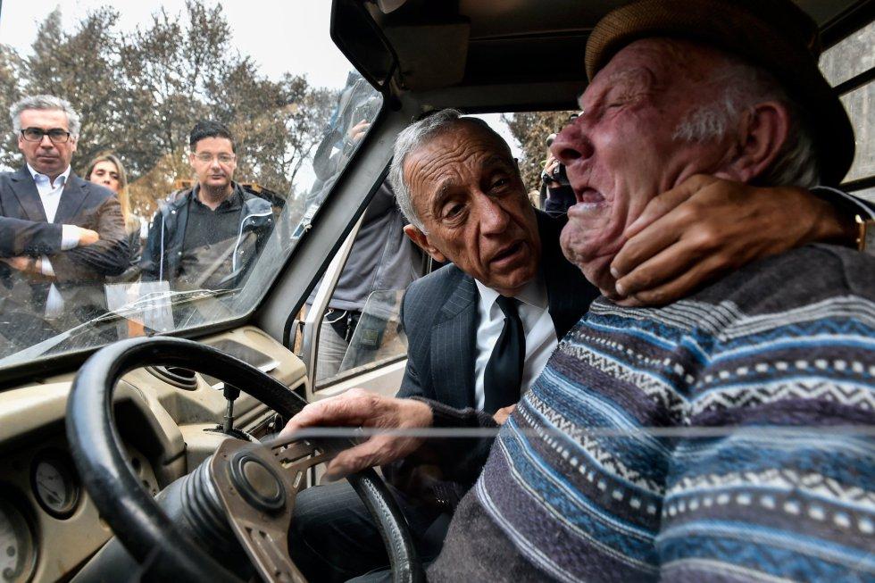 El presidente luso, Marcelo Rebelo de Sousa, consuela a un hombre mientras llora, durante una visita a los municipios del centro del país afectados por los incendios forestales de la semana pasada, en Santa Comba, Vouzela (Portugal).