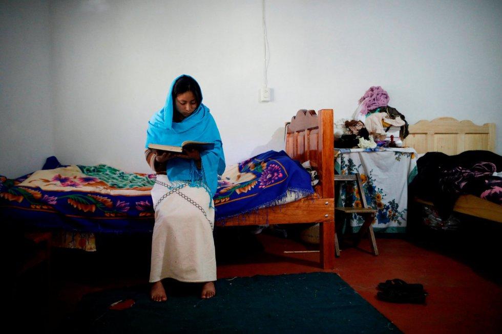 La joven Anisa lee el Corán encima de la cama de su vivienda.