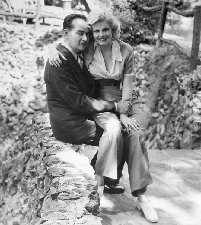 """Paul Bern (Alemania, 1889- California, 1932) fue un productor, director y guionista del primer Hollywood. Más de 2.000 personas asistieron a su funeral. La nota de suicidio dedicada a su esposa, la superestrella Jean Harlow, no encontró resolución porque ella aseguró no entender a qué se refería con """"esta es la única forma de arreglar lo que te he hecho y compensar mi humillación"""". La prensa, por su parte, sí que tenía una explicación: que Bern se suicidó porque era impotente. Las teorías van desde que fue asesinado por su primera mujer, quien días después se tiró de un ferry, hasta que la Metro-Goldwyn-Meyer ordenó su muerte porque él quería abandonar a Harlow tras sólo dos meses de matrimonio y el estudio no se podía permitir que su estrella más comercial quedase como una esposa torpe incapaz de retener a un marido. Enseguida la casaron con otro hombre, pero Harlow murió cuatro años después, en la cima de su carrera a los 26 años, víctima de una insuficiencia renal. En la imagen, el matrimonio Bern-Harlow, meses después de su boda, en 1932."""