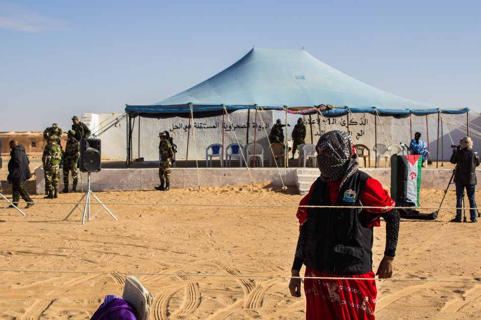 Esta mujer policía vigila la marcha conmemorativa del cuadragésimo primer aniversario de la creación de la RASD en el campo de refugiados de Auserd. La seguridad en los campos está muy reforzada debido a los peligros que existen en el desierto del Sahel. El contrabando de armas y drogas y el avance del extremismo islamista ponen en peligro la seguridad de los refugiados de Tinduf. A partir de la 1:00 está prohibido circular en coche por el campo de Auserd, donde se refuerza la vigilancia por las noches.