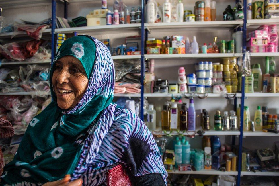 En 1975, España abandonó el Sáhara Occidental y estalló una guerra por el control del territorio entre el Frente Polisario (Movimiento de Liberación Nacional Saharaui), Marruecos y Mauritania. Las mujeres, los mayores y los niños que vivían en el Sáhara Occidental huyeron hacia Tinduf, región cedida por Argelia para asentarse temporalmente hasta que acabase el conflicto. Allí se erigió la República Árabe Saharaui Democrática (RASD), articulada por comités revolucionarios casi exclusivamente compuestos por mujeres. Existen cinco campos, donde actualmente viven 185.000 personas. En la foto, Fatimehtu Mahmud, que con 25 años tuvo que huir al desierto de Tinduf con su familia, dejando todo atrás. Vive en la  wilaya  (provinciacampo) de Auserd con su hija y sus nietas. Tiene 67 años y sus otras dos hijas viven en Canarias y Jerez, desde donde le mandan ayuda para subsistir. Dentro del campo hay un pequeño mercado donde los refugiados adquieren productos de primera necesidad, higiene y ropa. Los alimentos llegan a los campos a través de ayuda humanitaria.