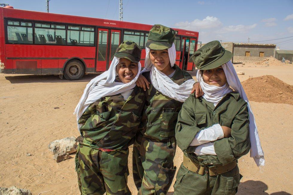 """Biya, Jadiyetu y su amiga (de 9 y 10 años) pertenecen a la escuela de Tichla, dentro del campo de Auserd. Van vestidas con uniforme por la marcha celebrada en honor a Brahim Gali, el nuevo secretario general del Frente Polisario que sustituyó a Mohammed Abdelaziz, fallecido el año pasado. La vestimenta militar representa el deseo de muchos saharauis de retomar la lucha armada. En el colegio, los niños y niñas cantan todos los días el himno saharaui mientras alzan la bandera antes de comenzar las clases. La letra habla de los mártires y el sufrimiento del pueblo saharaui. Verlos en fila recitando las palabras refleja una imagen rígida y jerárquica propia de un Estado militar. """"Marruecos tendrá que resolver este conflicto antes de que los jóvenes lleguen a la dirección política de la RASD, porque entonces no podrán pararlos"""", explica Mansur Mohammed Fedel, representante de la Unión de Jóvenes Saharauis (UJSARIO)."""