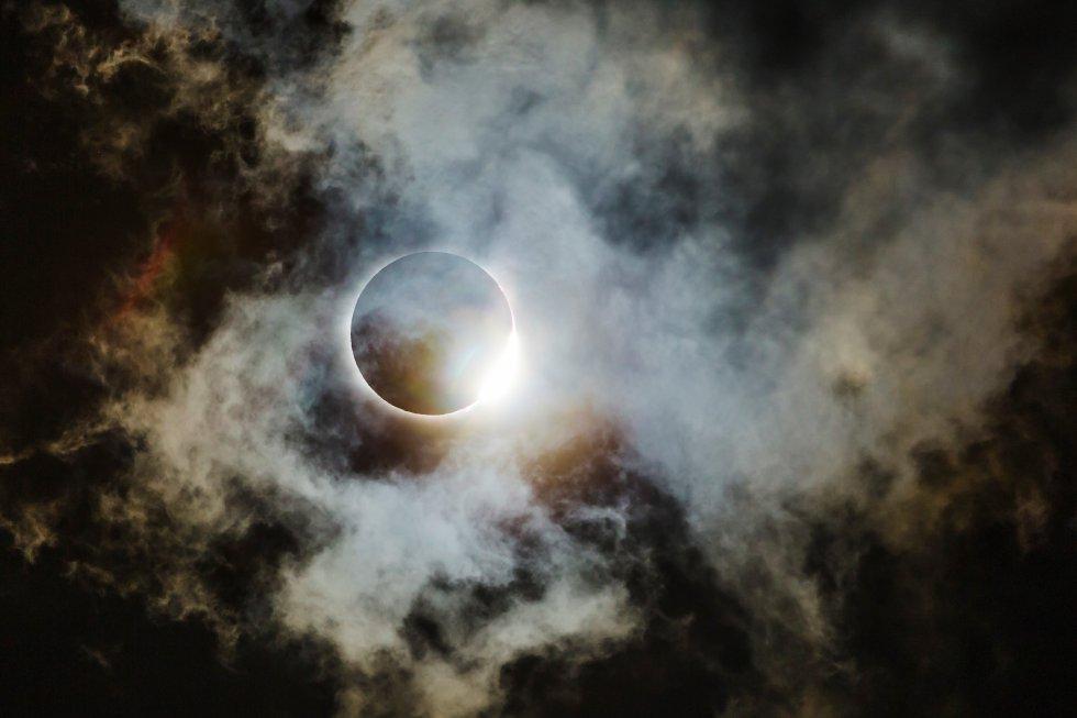 """Esta fotografía, finalista en la categoría Astronomía, muestra el eclipse estadounidense de 2017 que atravesó el norte de Georgia. Su autor, Wei-Feng Xue, afirma que en la imagen """"el anillo de diamantes ilumina algunas nubes muy finas, que parecen nubes espaciales""""."""