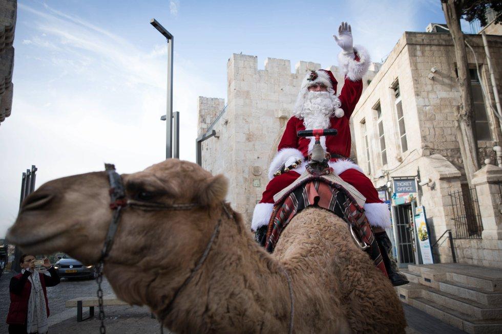 Papá Noel guía a su camello junto a las murallas de la antigua ciudad de Jerusalén, Israel.