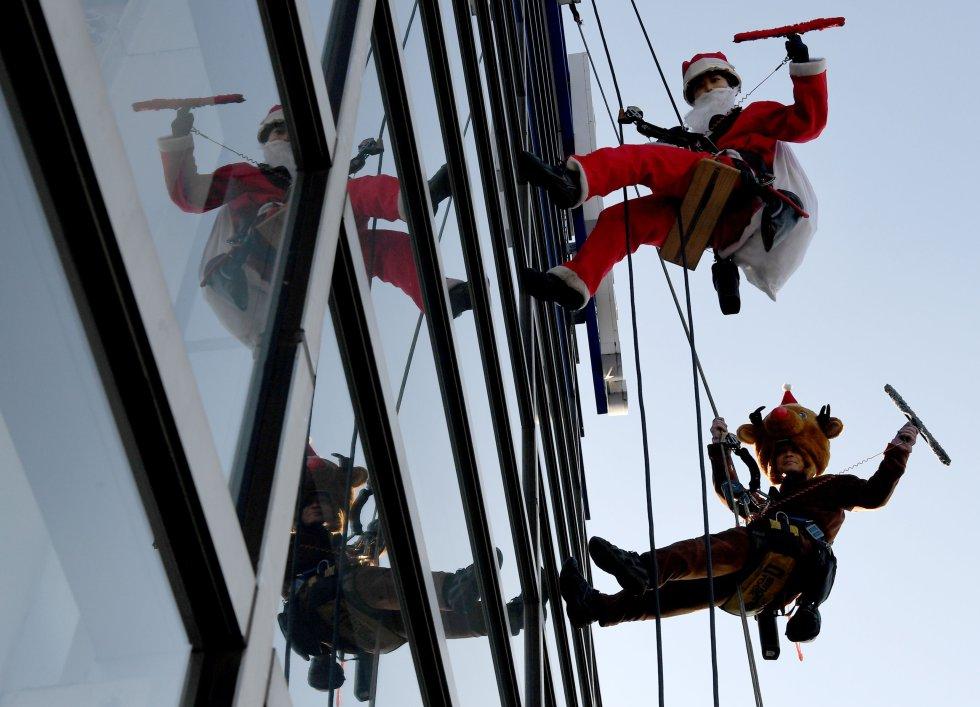 Como parte de su recorrido por varias partes del mundo, Papá Noel se dedicó a limpiar ventanas en un centro comercial de Tokyo.