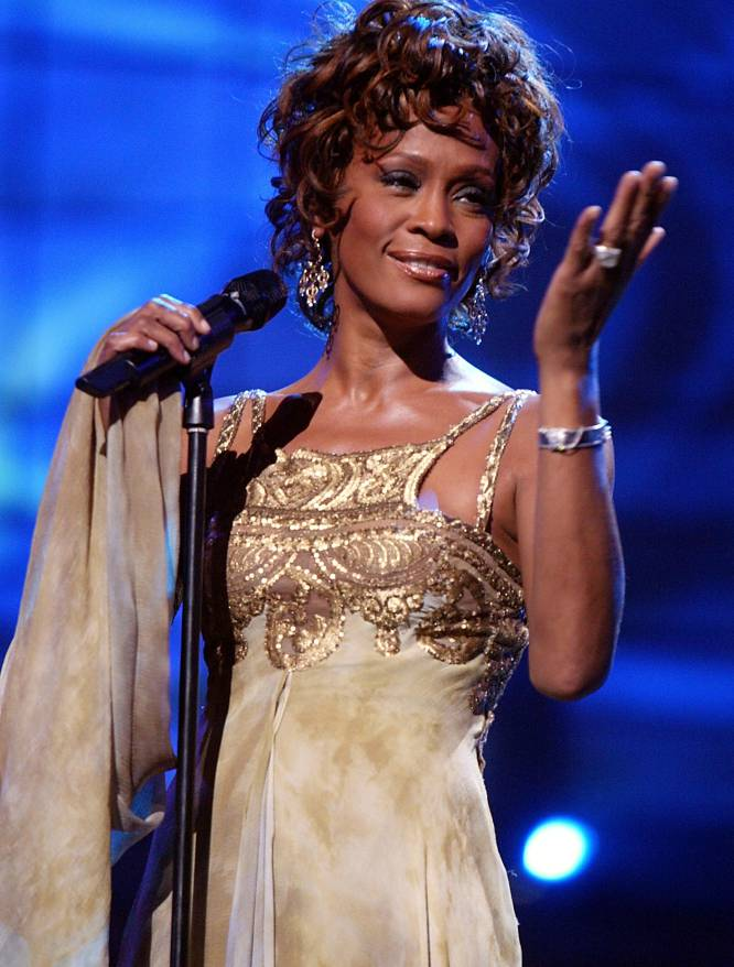 """Quando Whitney Houston (Nova Jersey, 1963-Los Angeles, 2012) foi encontrada morta na banheira de seu hotel em Los Angeles, em fevereiro de 2012, tinha teias de aranha em sua conta corrente e dívidas superiores a quatro milhões de dólares (quase 13 milhões de reais). Em apenas uma década, a cantora dilapidou sua fortuna pessoal de cerca de cem milhões (320 milhões de reais). Segundo o colunista social nova-iorquino Michael Lavelette, """"seu estilo de vida extravagante, seus muitos vícios (ao álcool, aos calmantes, à cocaína...) e seu divórcio de Bobby Brown a levaram à ruína"""". Seu último milhão foi gasto """"em um périplo delirante de vários meses por hotéis de luxo em Sidney, Paris e Londres no qual não prestou atenção aos gastos, apesar das advertências de seus assessores financeiros. Segundo divulgou a Fox News, poucas horas antes de morrer Houston tinha chamado uma amiga para pedir que lhe emprestasse 100 dólares que, supostamente, pensava em gastar em crack, a última droga em que se viciou. Na imagem, Whitney Houston no palco do World Music Awards de 2004, em Las Vegas."""