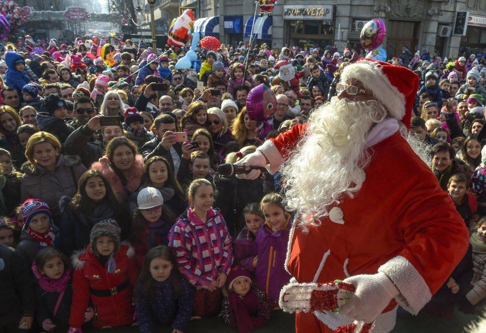 Un hombre vestido de Papá Noel saluda a los niños en la plaza principal de Skopje (Macedonia).