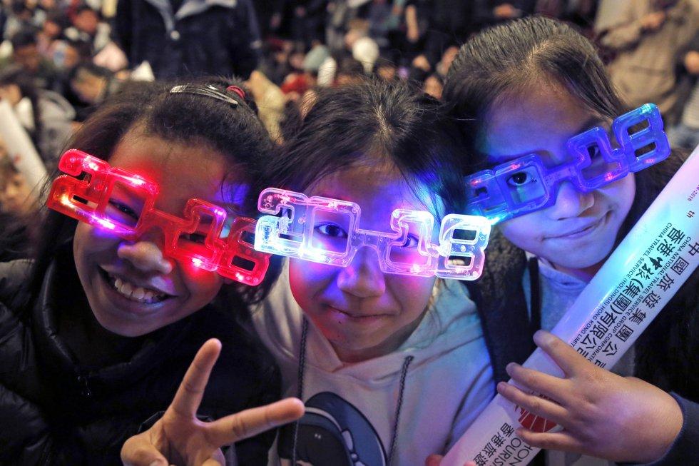 Un grupo de niñas con gafas esperan la llegada de 2018 en Hong Kong (Tokio).