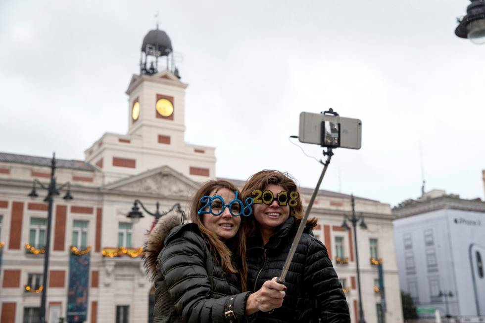 Dos mujeres se toman una foto en la Puerta del Sol de Madrid horas antes de la celebración de Año Nuevo.
