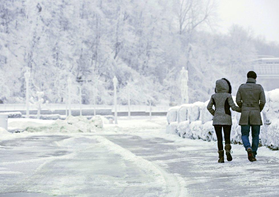 Os turistas chegam em massa, atraídos pelo impressionante espetáculo do grande salto d'água de mais de 60 metros, cujo lago serve como fronteira natural entre Estados Unidos e Canadá. Na imagem, um casal caminha perto da margem da catarata Horseshoe nas cataratas do Niágara, congeladas pela onda de frio polar.