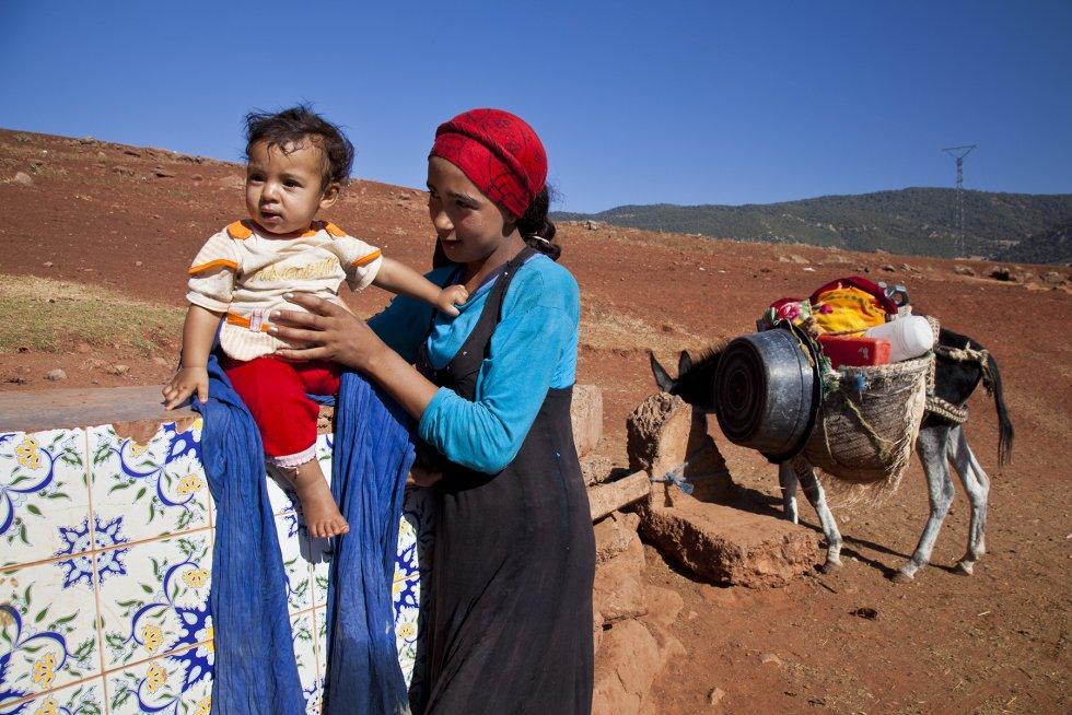 Mina, de 13 años, con su bebé en uno de las pocas fuentes que hay en la zona. Las mujeres son las encargadas de ir a buscar  el agua, y muchas veces tienen que recorrer muchos kilómetros para llegar al manantial.rnrn