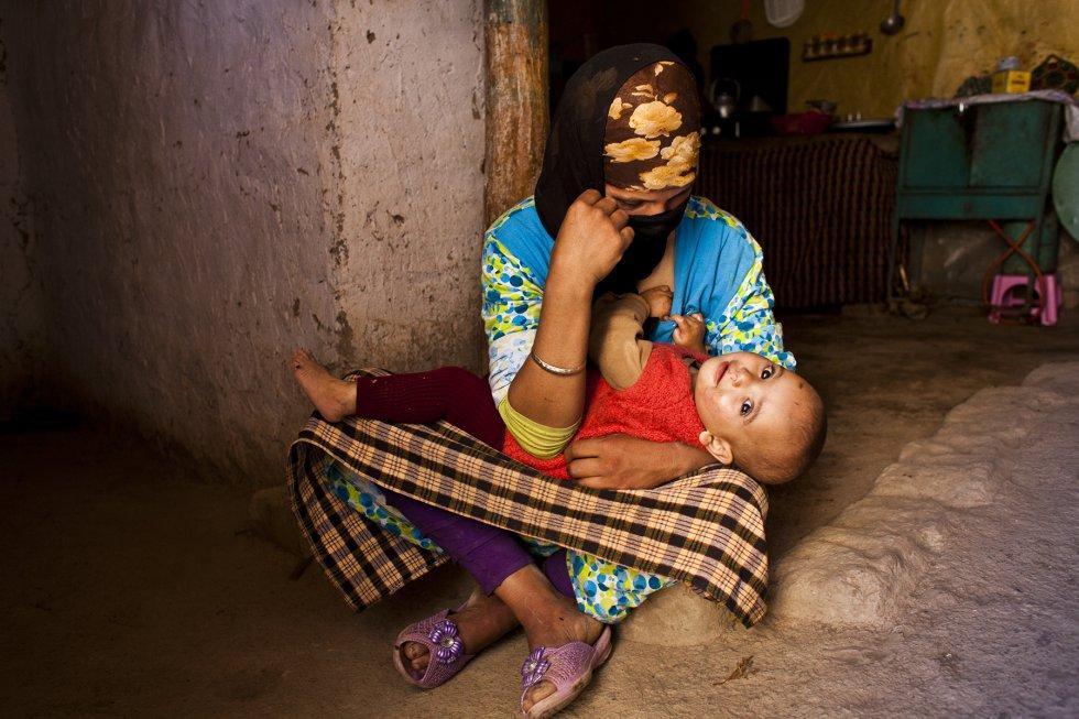 Nora, de 23 años, posa con su hijo pequeño en brazos en la aldea de N'Ihoudigne. Ella nunca estudió. Ha tenido a sus cuatro hijos en casa, asistida por su madre. Existe un alto nivel de mortalidad en las mujeres rurales de esta zona y en los niños menores de tres años. rn