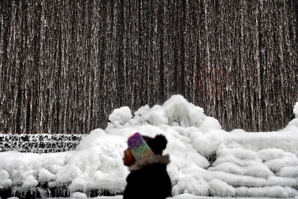 """A """"bomba meteorológica"""", equiparável a um furacão de inverno, está atingindo com dureza a Costa Leste dos Estados Unidos. Na imagem, um homem caminha junto a uma fonte congelada no centro de Atlanta, Georgia (EUA), na quarta-feira."""