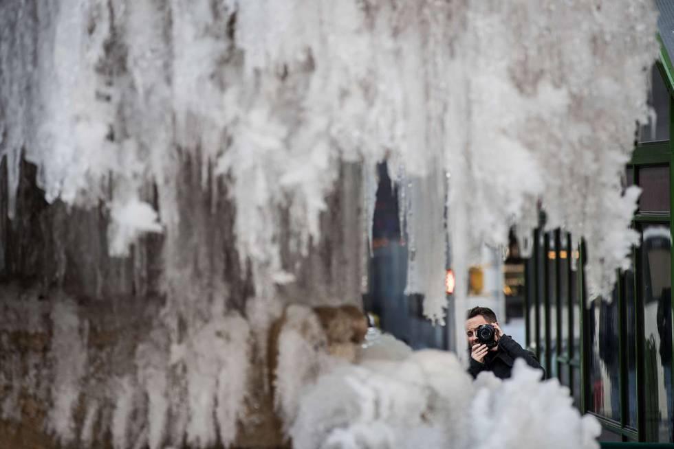 Homem faz foto em uma fonte congelada em Bryant Park, Nova York.