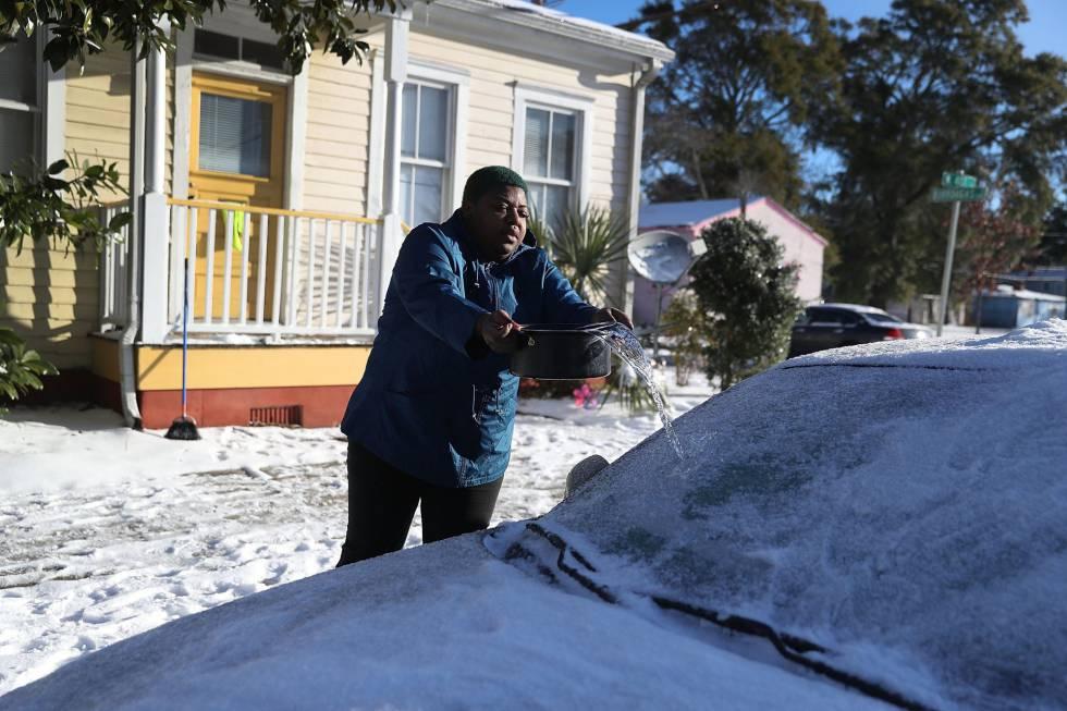 Mulher lança água no para-brisas de seu veículo em Savannah, no Estado de Georgia, nesta quinta-feira.