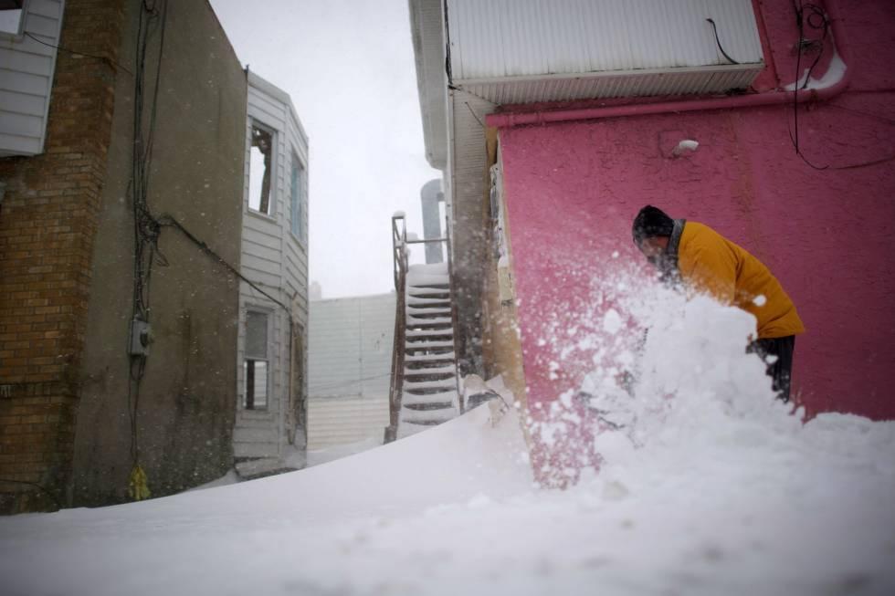 Um homem tira neve de uma rua em Atlantic City, nesta quinta-feira. Segundo as autoridades, a tempestade se estenderá da Flórida até o Maine, Estado fronteiriço com o Canadá, e cerca de 41 milhões de pessoas sentirão em maior ou menor medida o seu efeito. O pior, a potencial combinação de frio, neve e rajadas de vento poderosas, está previsto desde Boston até o nordeste, na região da Nova Inglaterra. As autoridades dos Estados dessa área temem especialmente que haja apagões enquanto as temperaturas alcançam níveis gélidos e, por isso, puseram em ação planos de emergência para prepararem albergues para indigentes e pessoas em situação vulnerável.