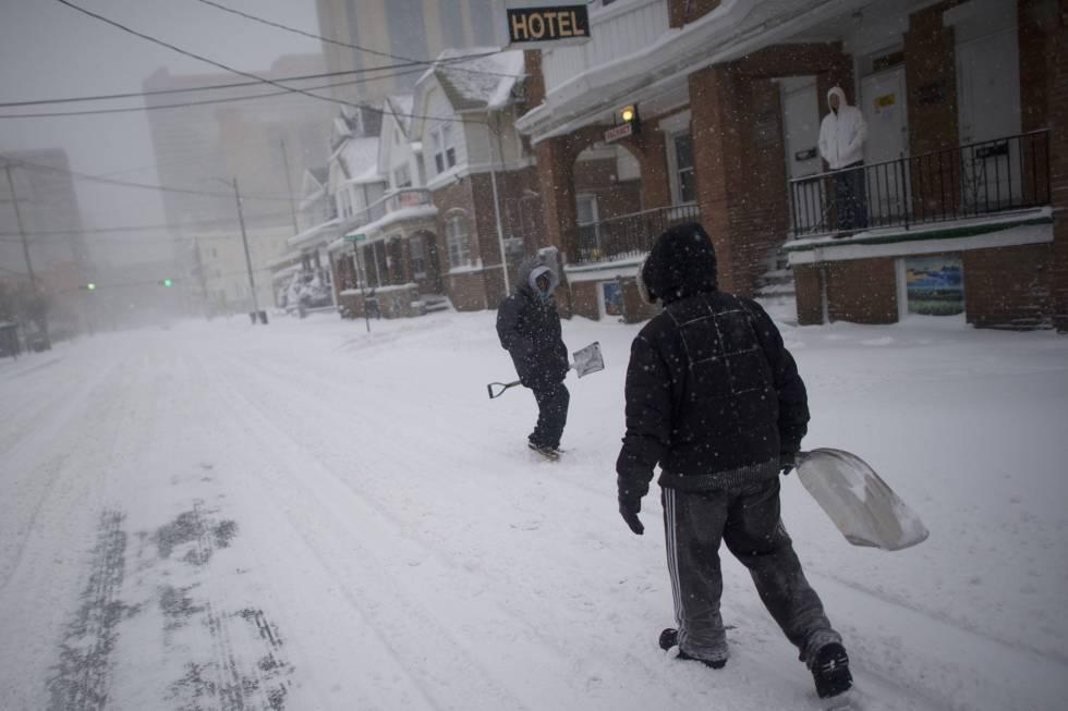 Dois homens com pás de neve em uma rua de Atlantic City. O ciclone de inverno prolonga uma sequência de dias de frio extremo que começou no dia do Natal na Costa Leste.