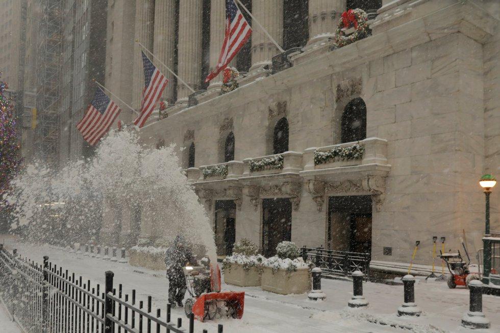 Um trabalhador limpa a neve em frente a edifício de Nova York (EUA). Em Washington, na quarta-feira, o aeroporto Dulles, nos arredores da capital, registrou uma mínima histórica de 17 graus centígrados abaixo de zero. Rajadas de vento de até 40 quilômetros por hora farão com que a sensação térmica em toda a região nordeste possa baixar entre três e cinco graus mais.