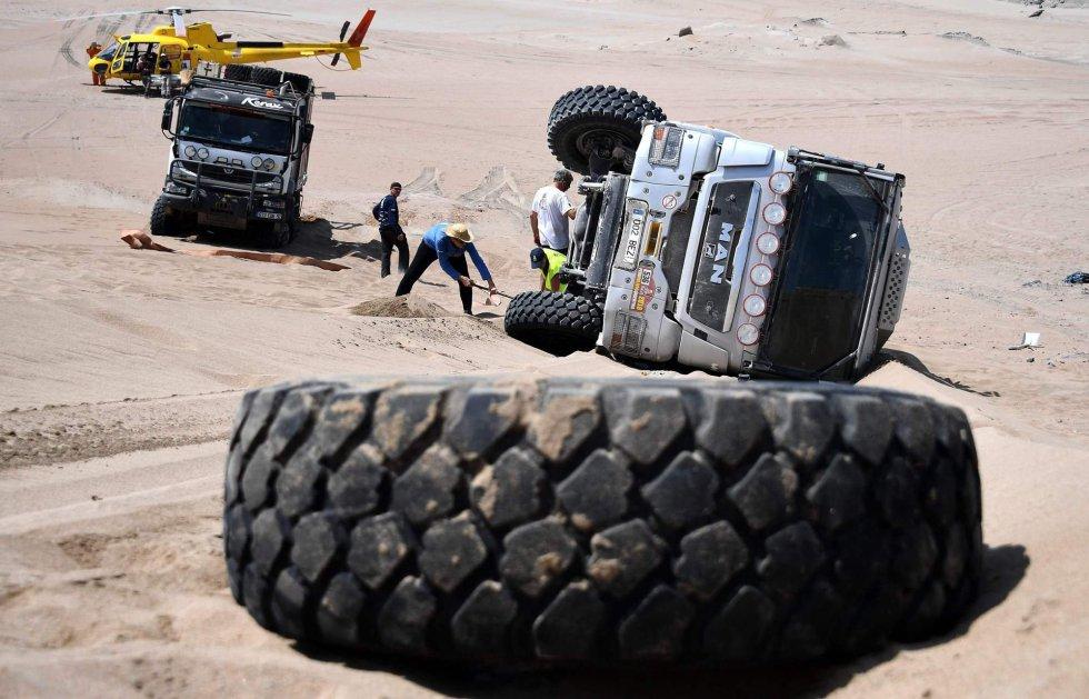Un grupo de personas intenta enderezar el camión conducido por Michel Saumet y Xavier Tancogne que se accidentó durante la tercera etapa del Dakar entre Pisco y San Juan de Marcona (Perú), el 8 de enero.