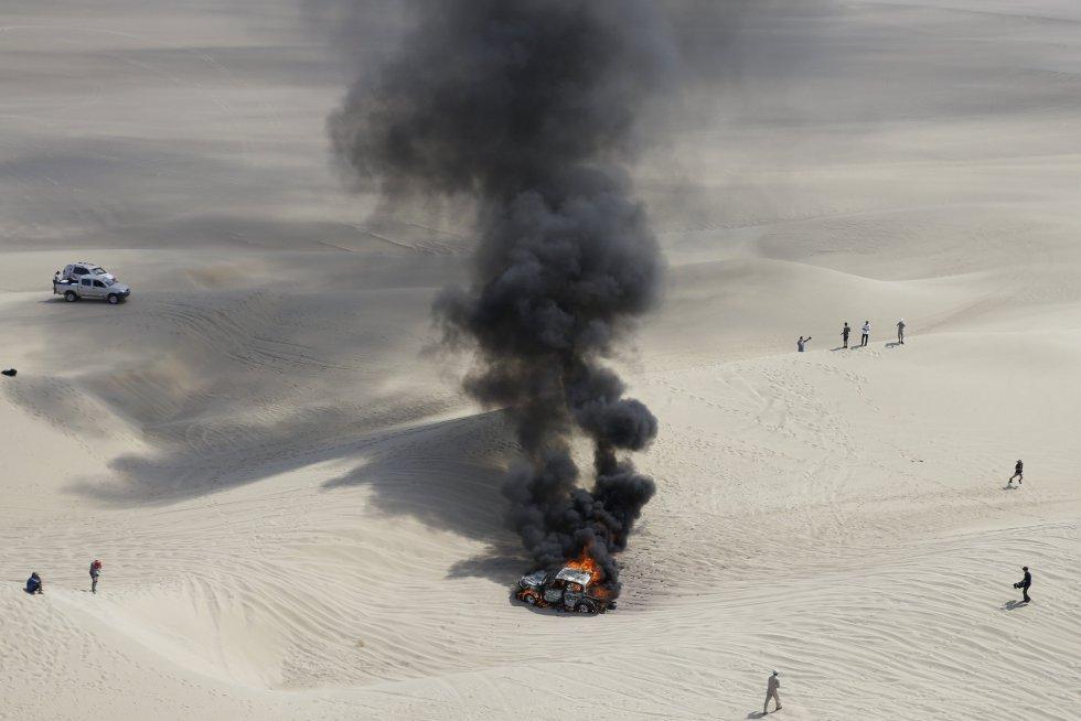 El coche de Alicia Reina y Carlos Dante Pelayo incendiado en la tercera etapa del Dakar en Pisco (Perú), el 8 de enero.