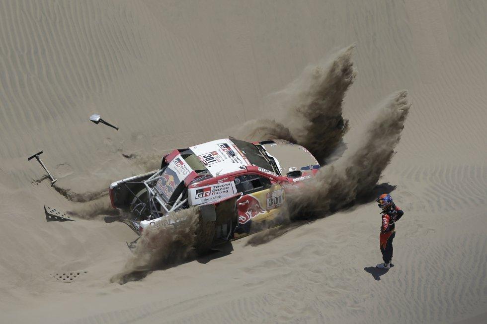 El copiloto Matthieu Baumel de Francia observa mientras el piloto Nasser Al-Attiyah de Qatar, intenta sacar de la arena su Toyota durante la cuarta etapa del Rally Dakar 2018 en San Juan de Marcona (Perú), el 9 de enero de 2018.