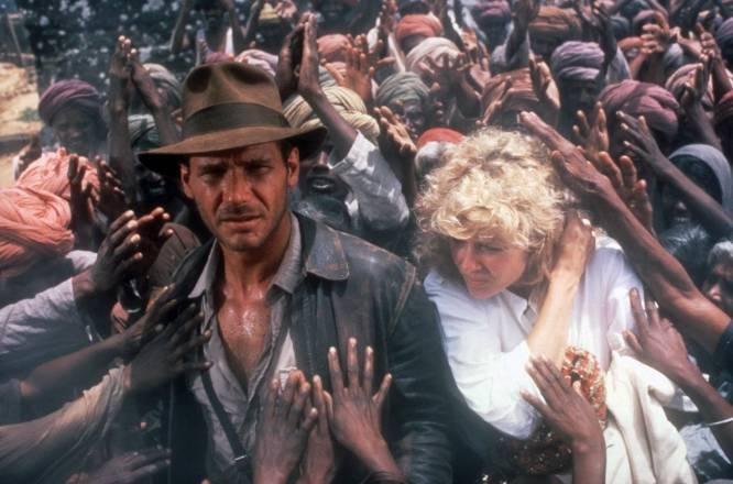 Lo que nos pareció en su momento.  En los 80, cualquier cosa con Indiana Jones era mejor que cualquier cosa sin Indiana Jones. Esta segunda parte, además, era la favorita de los chavales porque no dejan de pasar cosas, Indy se echa un amigo de 10 años y la trama es tan sencilla que se puede seguir mientras juegas con un cubo de Rubik.    Lo que es en realidad.  Un pasatiempo con el que Spielberg cumplió su sueño de dirigir una película de James Bond (el prólogo), se relajó mientras preparaba su primer gran drama ('El color púrpura') y cuyo personaje femenino él mismo ha confesado que representaba sus frustraciones durante su divorcio: Kate Capshaw (casualmente, su segunda mujer) se pasa dos horas gritando. La trama acumula persecuciones, pero ninguna acaba yendo en ninguna dirección.