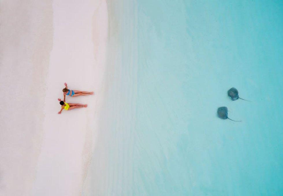 Dos chicas en la arena, dos mantas raya en el agua.