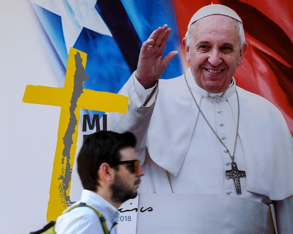 El hombre camina frente a uno de los carteles de bienvenida al Papa Francisco que fueron esparcidos por Santiago