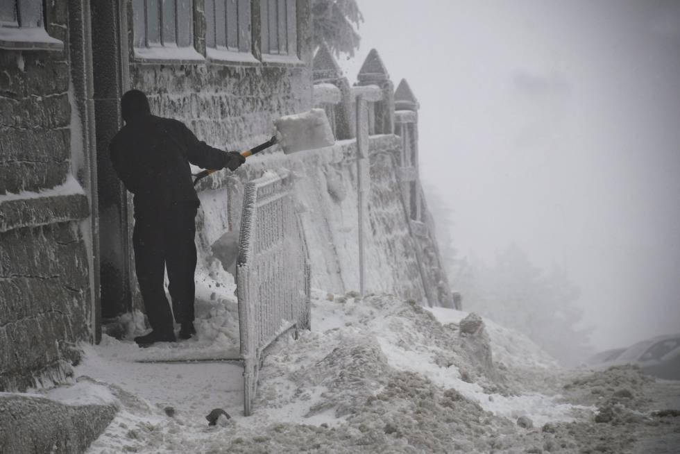 Un hombre retira la nieve de la puerta de una vivienda en el Puerto de Navacerrada, en la M-601, el 2 de febrero de 2018.