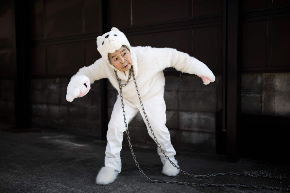 Kimiko Nishimoto, disfrazada de perro, posa como si estuviera encadenada a un poste.