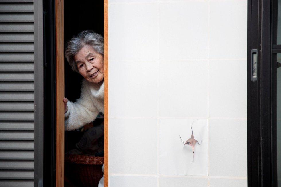"""La fotógrafa, Kimiko Nishimoto, posa junto a un retrato suyo en la ventana de su casa. """"Para ser sincera, no pienso mucho en lo que la fotografía significa para mí, solo entento traer alegría a la gente. Hacer fotos es el secreto de mi felicidad y seguiré haciéndolo mientras siga viva""""."""