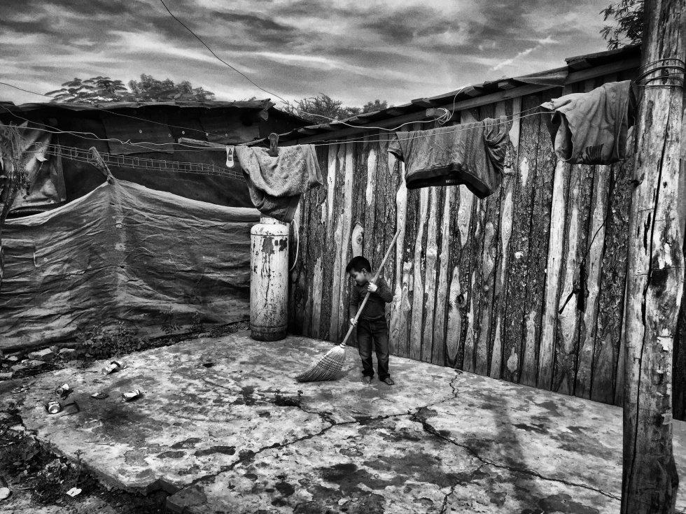 Marco Antonio, un niño de 8 años, limpia su improvisada casa de madera donde vive con sus padres y cuatro hermanos. Hasta hace 5 meses su vivienda estaba en la comunidad El Carrizal. Históricamente, los grupos de crimen organizado sinaloense han controlado ese territorio ya que es un punto geográfico estratégico para el tráfico de drogas desde México a Estados Unidos.