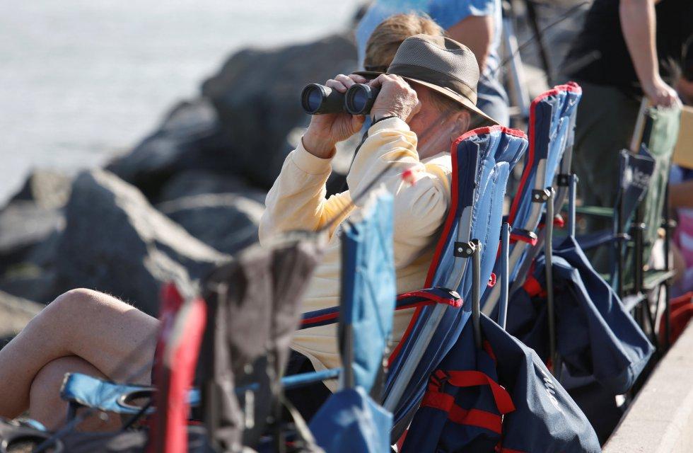 Un hombre sujeta sus prismáticos desde el sitio que ha conseguido para seguir el lanzamiento del cohete Falcon Heavy rocket en Cabo Cañaveral.