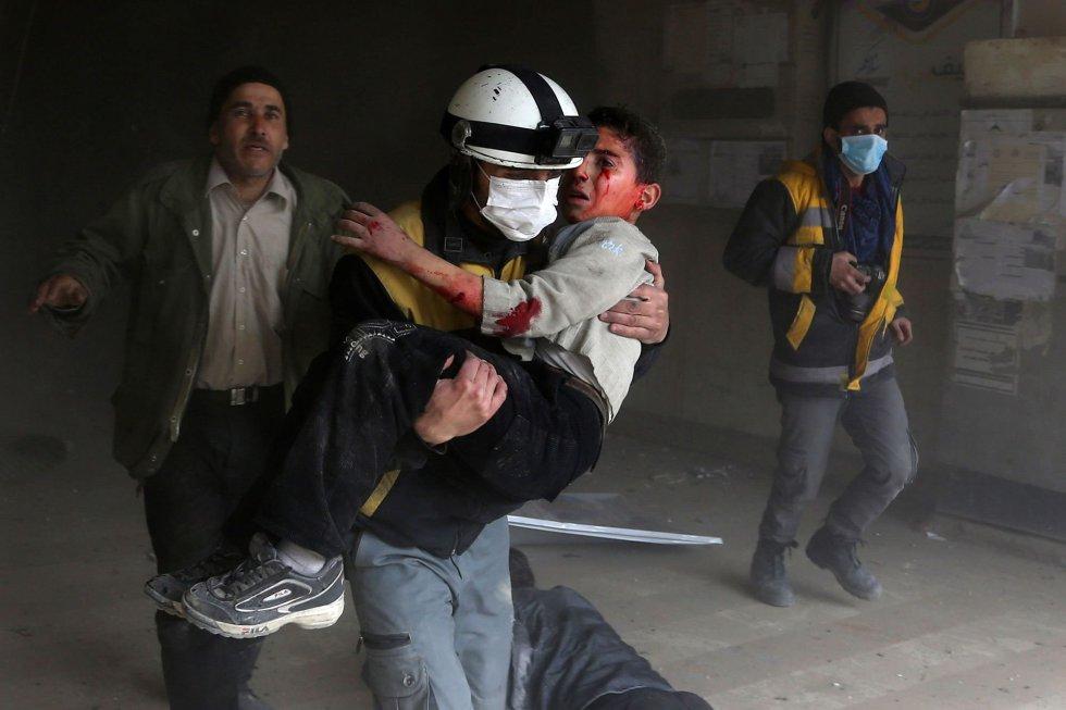 """UNICEF se ha sumado al llamamiento del cese inmediato de las hostilidades en Siria y ha recalcado que la protección de los niños """"debe ser una prioridad siempre"""". """"Las escuelas, hospitales y parques infantiles deberían ser sitios seguros, nunca objetivos de los ataques"""", ha apostillado. En la imagen, un grupo de rescate traslada a un niño herido durante la ofensiva, el 8 de febrero de 2018."""