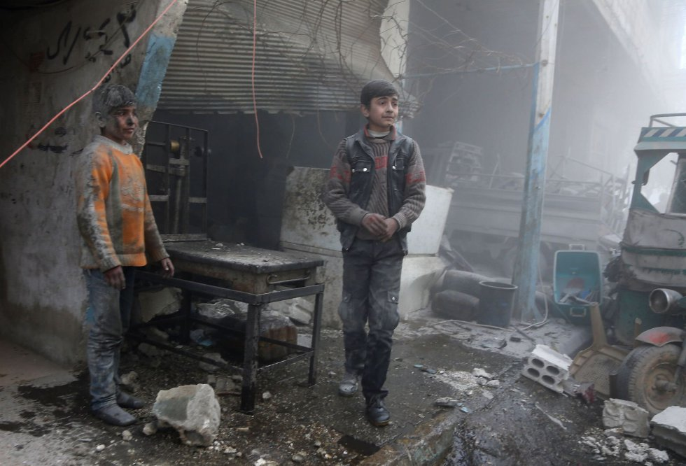 """Fore asegura que """"para los niños que siguen atrapados bajo el asedio deliberado y la violencia extrema en el país, la vida se ha convertido en una pesadilla. Están luchando por sobrevivir"""". En la imagen, dos niños esperan frente a una tienda destruida por los ataques aéreos, el 8 de febrero de 2018."""