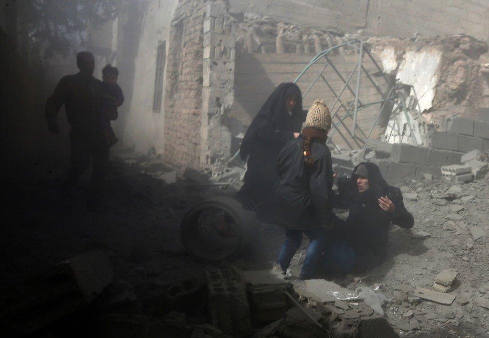 Una mujer siria es ayudada a levantarse durante la huida de los bombardeos, el 8 de febrero de 2018. De acuerdo con el Observatorio Sirio para los Derechos Humanos, desde el pasado 29 de diciembre han muerto en los bombardeos sobre Ghuta Oriental al menos 427 personas, entre ellas 105 niños.