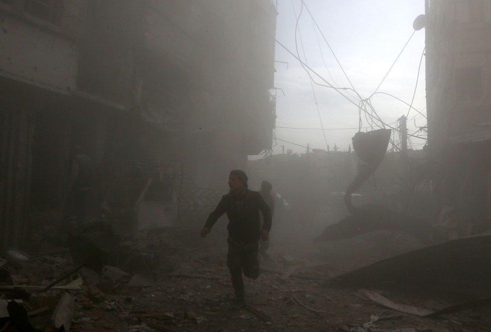Ghuta Oriental, en manos de los rebeldes y sitiada por el Ejército, fue designada como una 'zona segura', a pesar de lo cual las Fuerzas Armadas sirias han llevado a cabo bombardeos y ataques con artillería desde mediados de noviembre. En la imagen, civiles huyen de los ataques aéreos, el 8 de febrero de 2018.