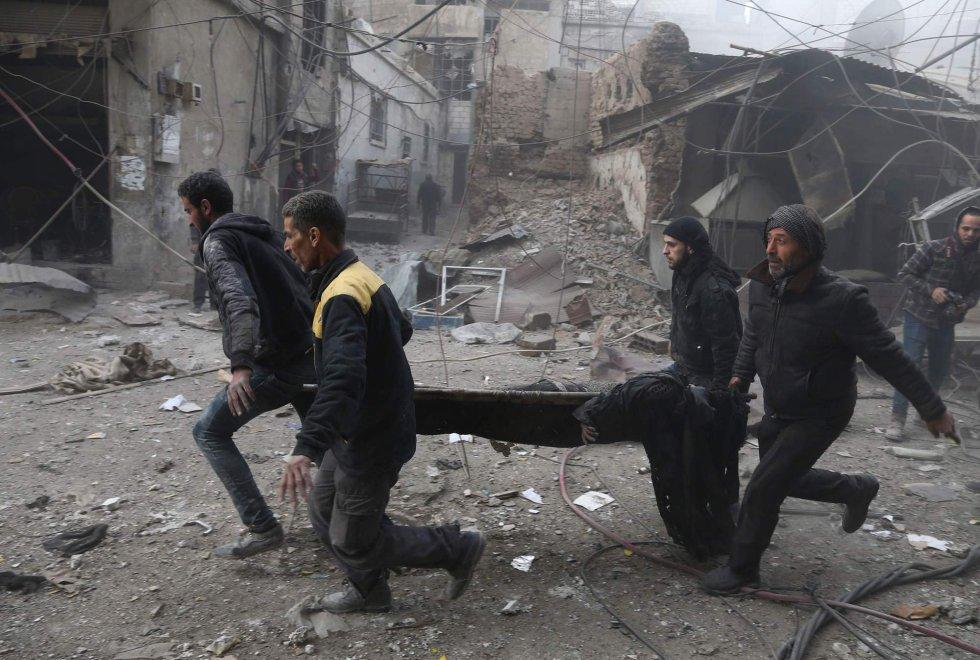 """El coordinador de Asuntos Humanitarios de la ONU, Marc Lowcock, aseguró el pasado diciembre que la situación de los cerca de 400.000 sirios atrapados en Ghuta Oriental es """"insoportable"""". En la imagen, un grupo de personas traslada a un herido, el 8 de febrero de 2018."""