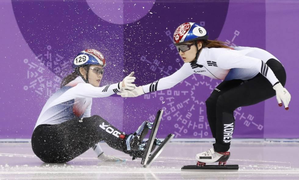 Choi Min-jeong de Corea del Sur ayuda a una compañera a levantarse tras caer a la pista durante la prueba de relevo de los 3.000 metros de velocidad en pista, el 10 de febrero de 2018.