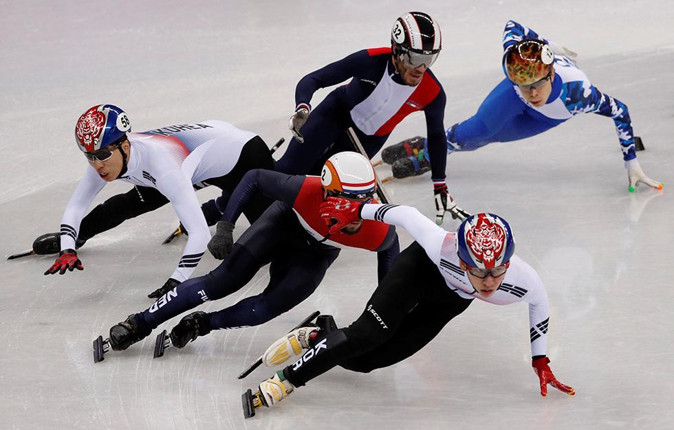 Lim Hyo-jun de Corea del Sur lidera por delante de Sjinkie Knegt de los Países Bajos cuando cae Hwang Dae-heon de Corea del Sur en la prueba de patinaje de velocidad en pista corta, el 10 de febrero de 2018.