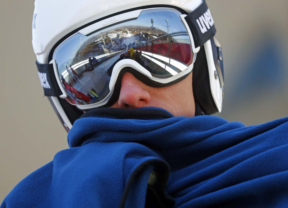 Viktor Pasichnyk, da Ucrânia, se esquenta com um cobertor antes da prova de salto de esqui.