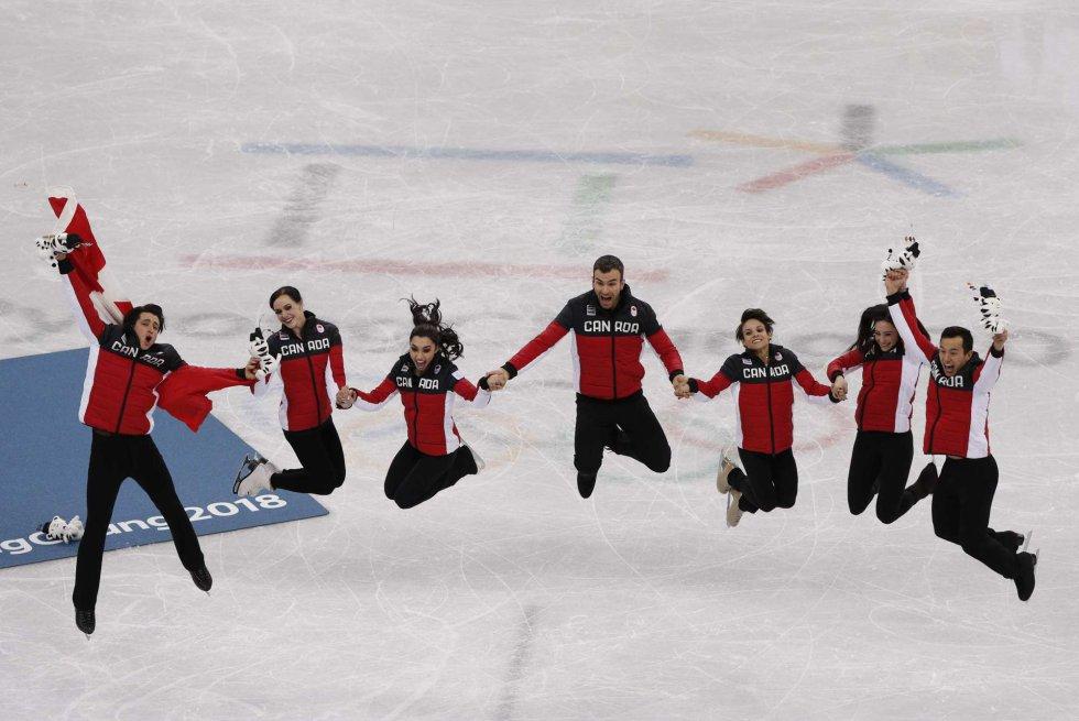 Os medallista de ouro da equipe de patinação artística do Canadá celebram a vitória no Gangneung Ice Arena.