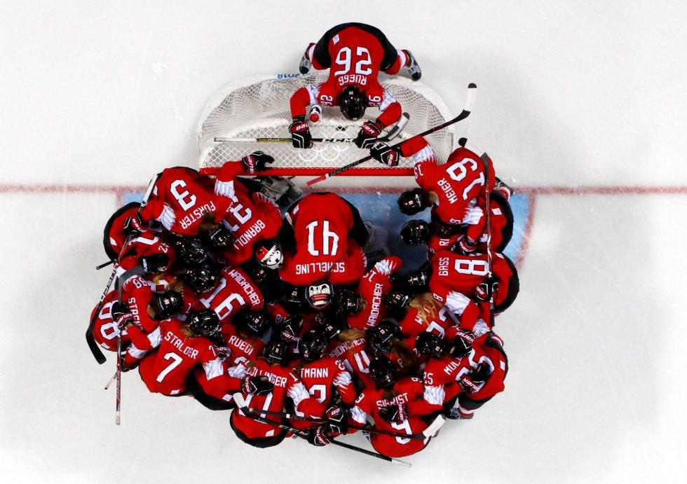 A equipe suíça feminina de hóquei no gelo se concentra antes de sua partida frente ao Japão.