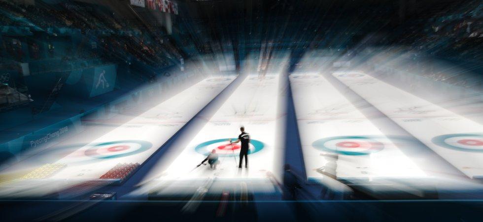 Os atletas russos Anastasia Bryzgalova (esquerda) e Aleksandr Krushelnitckii (direita) jogam contra os suíços Jenny Perret e Martin Rios durante a partida de semifinais de duplas mistas no Gangneung Curling Center.