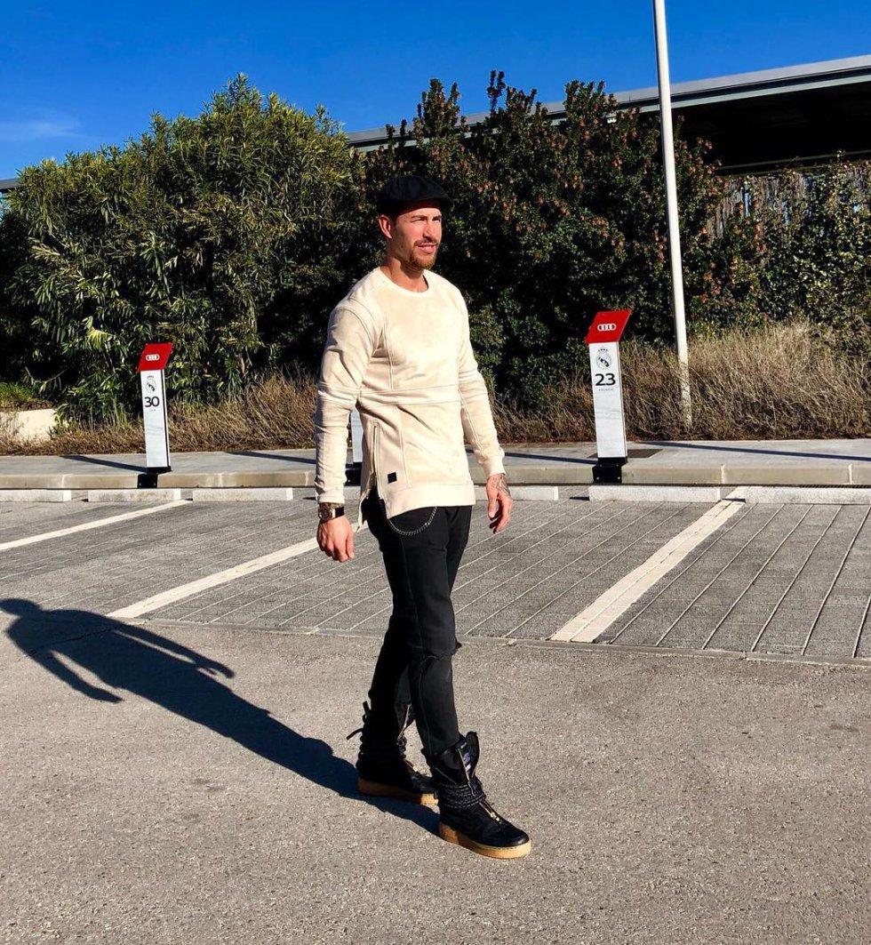 Para su regreso a los entrenamientos en la ciudad deportiva del Real Madrid tras el parón navideño, Ramos eligió un conjunto que constaba de unos pantalones vaqueros negros adornados con cadenas, una camiseta color crema y completó su 'look' con una boina calada y unas botas negras estilo militar abiertas en la parte delantera.